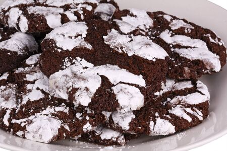 Mound of home-made chocolate crinkle cookies against a white background photo
