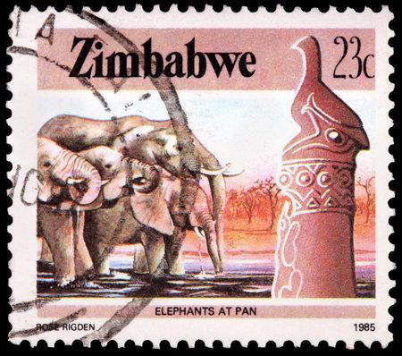 zimbabwe: ZIMBABWE - CIRCA 1985: Un sello de 23 centavos de dólar impreso en la República de Zimbabwe muestra varios elefantes en la bandeja de agua potable, alrededor de 1985 Editorial