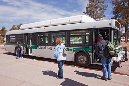 GRAND CANYON, AZ - MARCH 23: Visitors board a south rim shuttle bus at Grand Canyon Visitors Center on March 23, 2011. The free buses are powered by compressed natural gas and reduce park traffic.