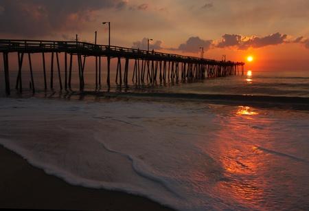 nags: Los rayos del sol iluminan un muelle de pesca, el mar y la espuma de una playa en Nags Head, Carolina del Norte