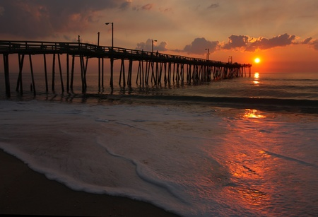 Rays from the rising sun illuminate a fishing pier, the ocean and foam from a beach in Nags Head, North Carolina Stock Photo