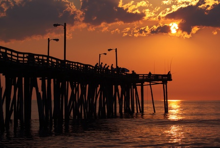 Early-morning anglers are silhouetted against the rising sun on a fishing pier in Nags Head, North Carolina photo