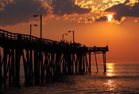 nags: Temprano por la ma�ana los pescadores est�n en silueta contra el sol que se levanta en un muelle de pesca en Nags Head, Carolina del Norte