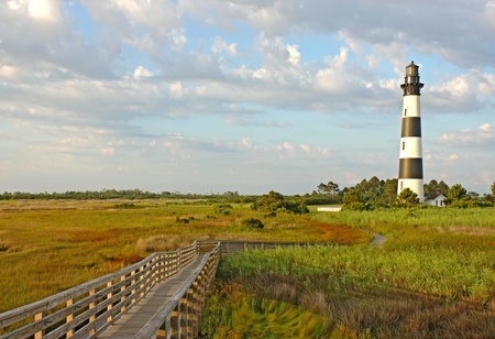 Walkway leading to the Bodie Island lighthouse over marshes of the Cape Hatteras National Seashore against white clouds and a blue morning sky Stock Photo - 13454822