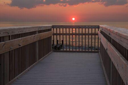 nags: El sol est� justo sobre el horizonte sobre el oc�ano Atl�ntico en la madrugada en un acceso a la playa p�blica en Nags Head, Carolina del Norte