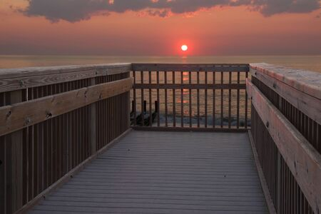 bank of america: The sun is just above the horizon over the Atlantic ocean in early morning at a public beach access in Nags Head, North Carolina