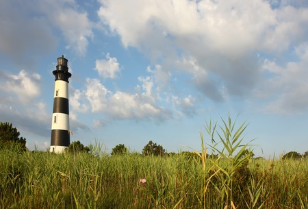 The Bodie Island lighthouse over marshes of the Cape Hatteras National Seashore on the Outer Banks of North Carolina against white clouds and a blue morning sky photo