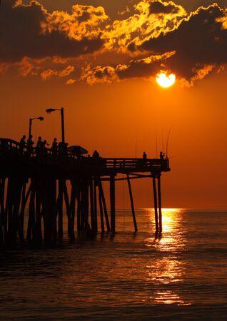nags: Temprano por la ma�ana los pescadores est�n en silueta contra el sol que se levanta en un muelle de pesca en Nags Head, Carolina del Norte verticales