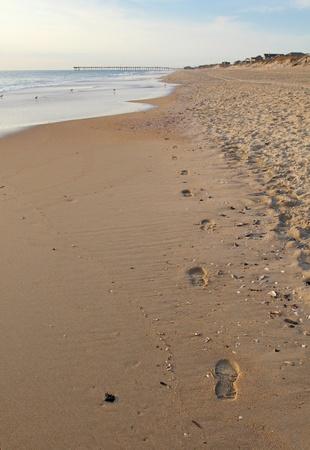 nags: Un solo par de huellas a lo largo de la playa vac�a en la madrugada en los Outer Banks de Carolina del Norte con las casas de playa y un muelle de pesca en el fondo Foto de archivo