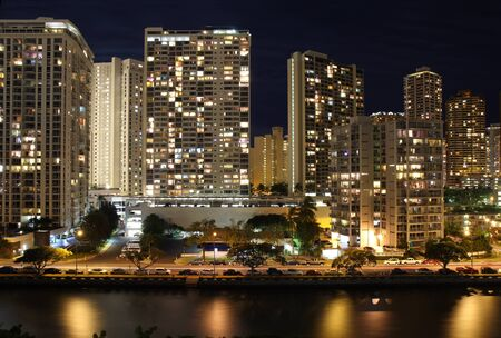 Office buildings and apartments form a partial skyline of Honolulu along the Ala Wai Canal near the Hawaii Convention Center at night photo