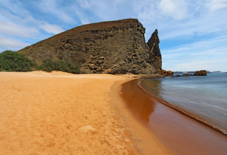 View of Pinnacle Rock and breaking waves from the red sand beach on Bartolome Island, Galapagos National Park, Ecuador, with Sullivan Bay, cruise ships, and Santiago Island in the background 版權商用圖片