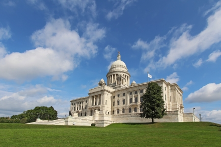 Wide-angle view of the front of the Rhode Island state capitol building as it sits on Capitol Hill in Providence with bright blue sky and white clouds in the background  The building is covered with white Georgia marble and was constructed from 1895 to 19