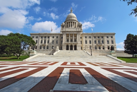 Wide-angle view of the front of the Rhode Island state capitol building with red and white brickwork in Providence with bright blue sky and white clouds in the background  The building is covered with white Georgia marble and was constructed from 1895 to