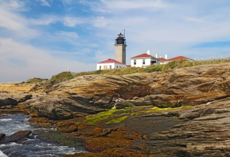 The Beavertail Light lighthouse near Jamestown on Conanicut Island, Rhode Island, viewed from the rocky coast with a bright blue sky and white clouds