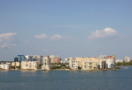 high rise buildings: View of buildings on the edge of  Sarasota Bay, Sarasota, Florida from the water with palm trees and a blue sky