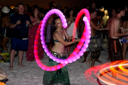 mov: SIESTA KEY, FLORIDA - MAY 22: Dancers twirling colored perform in the center of a drum circle on Siesta Key Public Beach near Sarasota, Florida, May 22, 2011.  A slow shutter speed gives motion blur to the dancers colored lights and spectators as they mov