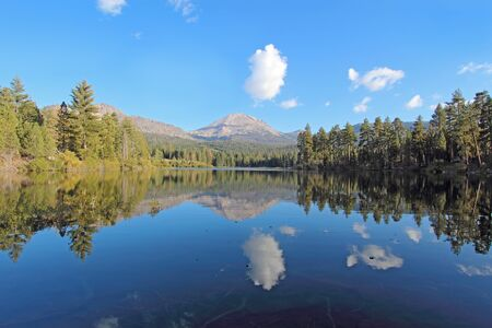 Wide-angle view of Lassen Peak, trees and white clouds reflected in the calm waters on Manzanita Lake near the entrance to Lassen Volcanic National Park in northern California photo