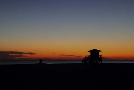 lifeguard tower: HDR image of a lifeguard station on Siesta Key Beach, Florida silhouetted against the setting sun with a dark blue and orange sky