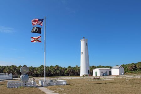 north   end: Lighthouse, flags and associated buildings at the north end of Egmont Key, a small island near the mouth of Tampa Bay, Florida