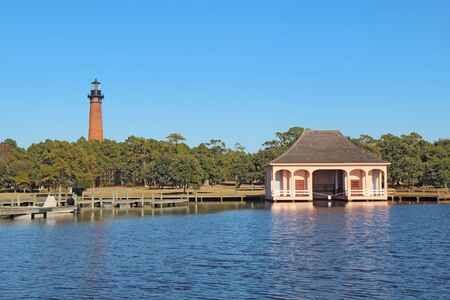 corolla: The red brick structure of the Currituck Beach Lighthouse and the pink boathouse at Currituck Heritage Park near Corolla, North Carolina Stock Photo