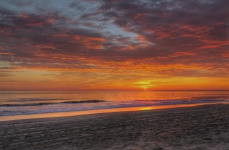 amanecer: Dramático nubes ocultan el sol, ya que se eleva sobre el océano Atlántico para iluminar la playa de arena en Nags Head en los Outer Banks de Carolina del Norte Foto de archivo