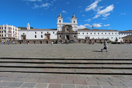 QUITO, ECUADOR - JUNE 1  People go about their business in the plaza in front of the church and convent of San Francisco in the historic part of downtown Quito, Ecuador against a bright blue sky and white clouds on June 1, 2012