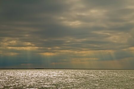 outer banks: Rays of the sun pierce the clouds and sparkle on the waters of the Oregon Inlet into Pamlico Sound on the outer banks of North Carolina