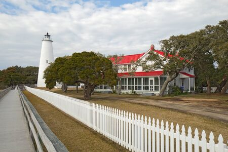 north carolina: White picket fence and walkway lead past the red-roofed keepers quarters towards the tower of the Ocracoke Island lighthouse on the outer banks of North Carolina, the second-oldest operating lighthouse in the United States