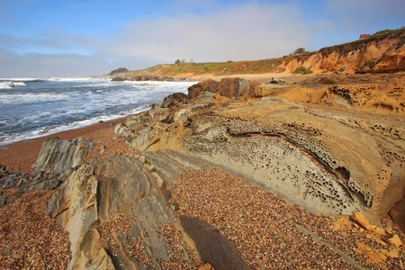 concave: Pebble Beach and tafoni formations in Pigeon Point formation sandstone at Bean Hollow State Beach in San Mateo County, California against a blue sky and white clouds