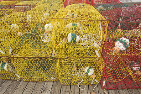 crab pots: Yellow and red crab pots sit on a dock in Ocracoke Island, NorthCarolina, awaiting their deployment in Pamlico Sound