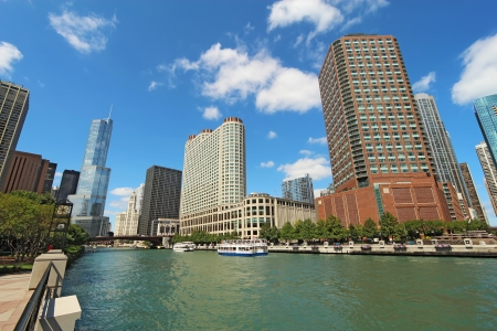 tour boats: Tour boats and the city skyline along the Chicago River in Chicago, Illinois against a bright blue sky with white clouds