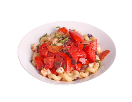 cubed: Plate of home-made, cold cavatappi or cellentani pasta salad  pasta fredda  with fresh basil and tomatoes, black Kalamata olives, sliced pepperoni, cubed mozzarella cheese and dried herbs isolated against a white background Stock Photo