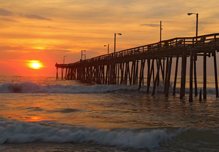obx: The rising sun peeks through clouds and is reflected in waves by the Nags Head fishing pier on the outer banks of North Carolina