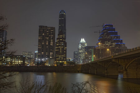 partial skyline of Austin, Texas over the water of Lady Bird Lake at night photo