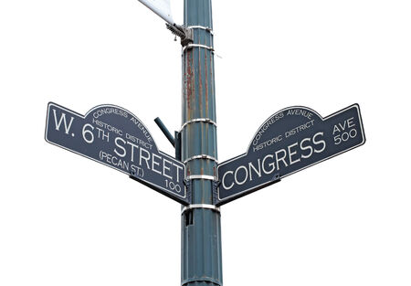 sixth: Sign at the intersection of West 6th Street (Pecan Street) and Congress Avenue in the Congress Avenue historic district at the bustling center of Austin, Texas, isolated against white