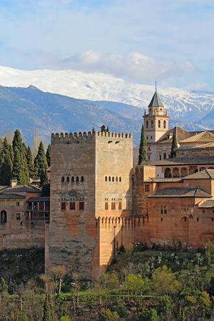 granada: Part of the Alhambra palaces and fortifications including the Comares Tower against the Sierra Nevada mountains of Granada, Spain vertical