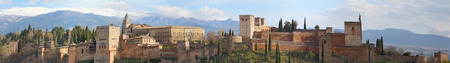 Panoramic view of the Alhambra palaces and fortifications in Granada, Spain against a background of the Sierra Nevada mountains