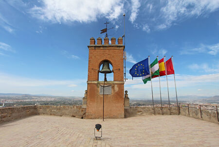 crenellated: Flags and a crenellated bell tower at the highest point of the Alcazaba fortress of the Alhambra in Granada, Spain Stock Photo