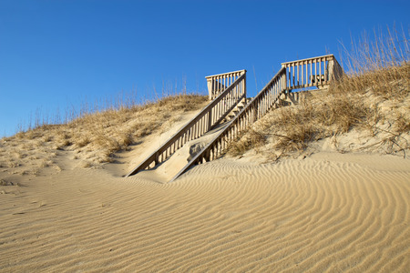 nags: Sand-covered stairway to a public beach in Nags Head on the Outer Banks of North Carolina against a bright blue sky