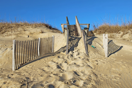 obx: Dilapidated, sand-covered stairway to a public beach in Nags Head on the Outer Banks of North Carolina against a bright blue sky