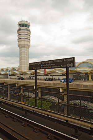 ronald reagan: ARLINGTON, VIRGINIA - JULY 21 2014: Washington DC metro sign and control tower for Ronald Reagan National airport. The airport has very tight security and is the main gateway into the US capital city.