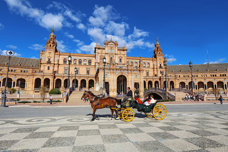 espana: SEVILLE, SPAIN - MARCH 26 2014: Tourists and a horse-drawn carriage in front of the Plaza de Espana in Seville, Spain. The Plaza is a major tourist destination that was built in 1928. Editorial