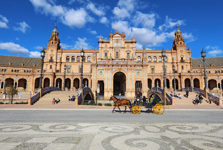 espana: SEVILLE, SPAIN - MARCH 26 2014: Tourists ride a horse-drawn carriage in front of the Plaza de Espana in Seville, Spain. The Plaza is a major tourist destination that was built in 1928.