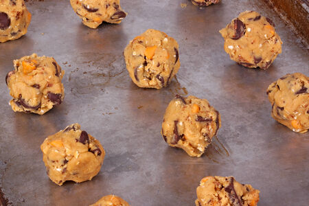 Balls of home-made chocolate and butterscotch chip and oatmeal cookie dough on a pan ready to be baked photo