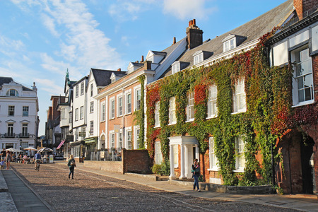south west england: EXETER, UK - SEPTEMBER 12 2014: Pedestrians walk by businesses and residences on Cathedral Close and Cathedral Yard. This is a popular area for tourists and residents to relax near Exeter Cathedral.