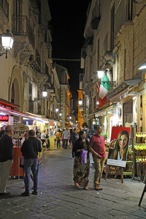 sorrento: SORRENTO, ITALY - OCTOBER 9 2014: Tourists on Via San Cesareo in downtown Sorrento, Italy at night. This pedestrian shopping street is a popular destination for tourists to shop and visit restaurants.