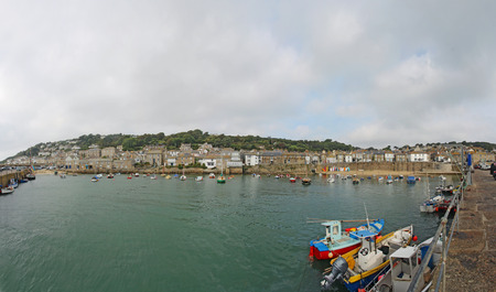 mousehole: Panoramic view of the circular harbor at Mousehole, a small village and fishing port on the southern coast of Cornwall, England, United Kingdom
