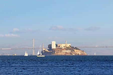 Boats sail past Alcatraz Island in San Francisco Bay, California with the San Francisco�Oakland Bay Bridge in the background photo