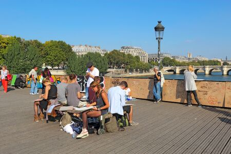 locks: PARIS, FRANCE - SEPTEMBER 10 2014: Students doing plein air sketches on the Pont des Artes. This pedestrian bridge over the Seine is very popular with students, artists, photographers and lovers. Editorial