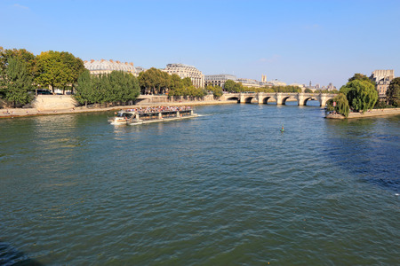 rive: PARIS, FRANCE - SEPTEMBER 10 2014: Tourist boat on the river Seine near the right bank, Pont Neuf and the Ile de la Cite. These boats are popular with tourists for views along both banks of the river.